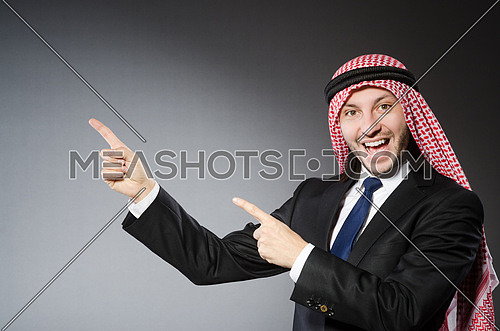 Arab businessman pressing virtual buttons against grey background