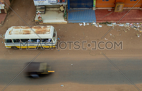 a top shot showing a bus and a tok tok speeding in an empty street in Sudan