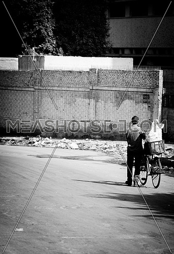 Vintage CairoBlack & white photoset from the bridge of Imbaba; that was built in 1912 & 1924 in Egypt. A Man walking and dragging his bike.