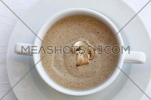 Portion of champignon mushroom cream soup in white porcelain tureen pot on the table, close up, high key, elevated top view
