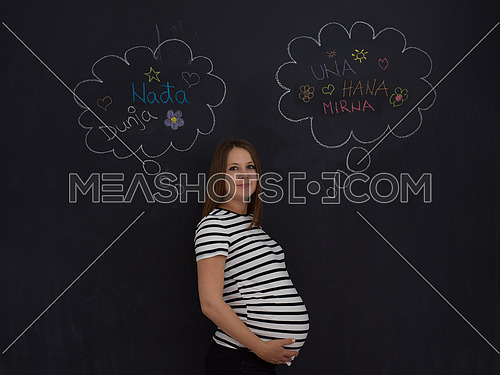 young pregnant woman thinking about names for her unborn baby to writing them on a black chalkboard
