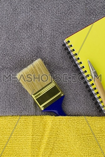 Colorful yellow and grey themed still life with clean paintbrush and yellow wire bound notepad on a two tone grey and yellow textile background
