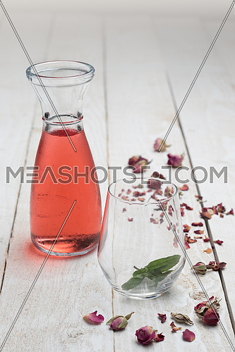 Glass of red solution and an empty glass on a wooden background