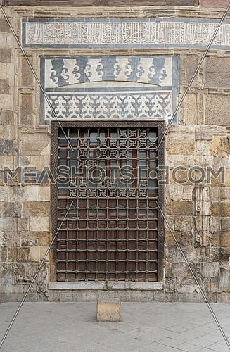 Wooden window with decorated iron grid over stone bricks wall at Madrasa and Mausoleum of As-Saleh Nagm Ad-Din Ayyub, Medieval Cairo, Egypt