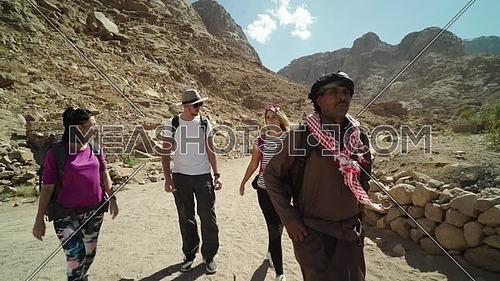 Reveal shot for group of tourists walking with bedouin guide exploring Sinai Mountain from wadi Freij at day.