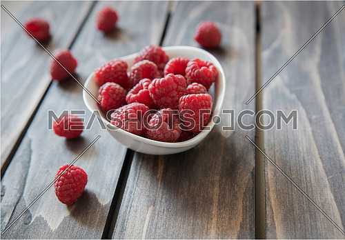 Ripe tasty raspberries on wooden background. Healthy and diet food. Organic berries. Selective focus