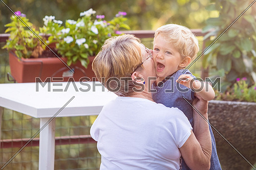 Grandmother hugs and gently kisses her grandchild in garden, natural light.