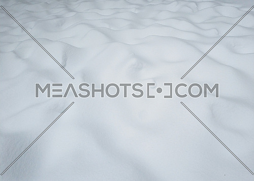 Background texture of uneven white snow surface pattern on ground with snowdrift sites, cold winter day, high angle view