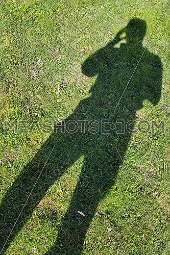 Stress, headache, health care and people concept: man's shadow projected on green grass with hand to his head