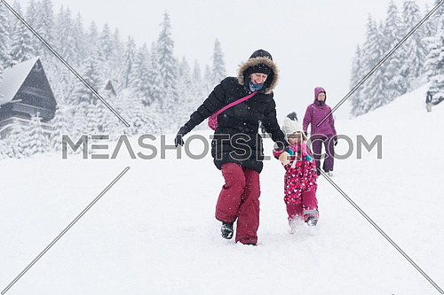 happy family on winter vacation, portrait of mother  and cute little girl have fun and slide while snow falkes falling