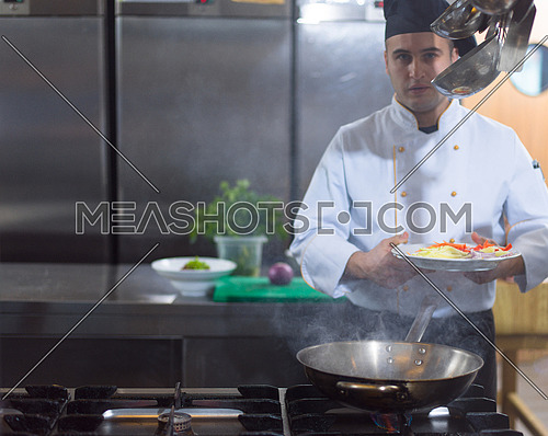 Master chef preparing food, frying in wok pan. Sale and food concept