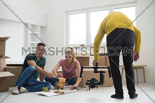 happy young couple have a pizza lunch break on the floor after moving into a new home with boxes around them