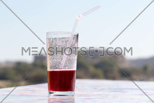 Glass of cold hibiscus and a straw in it