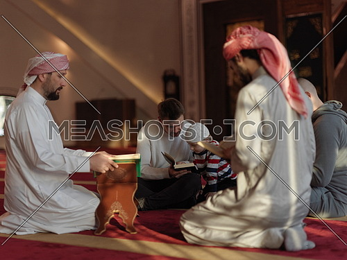muslim people in mosque reading quran together concept of islamic education and school of holly book kuran