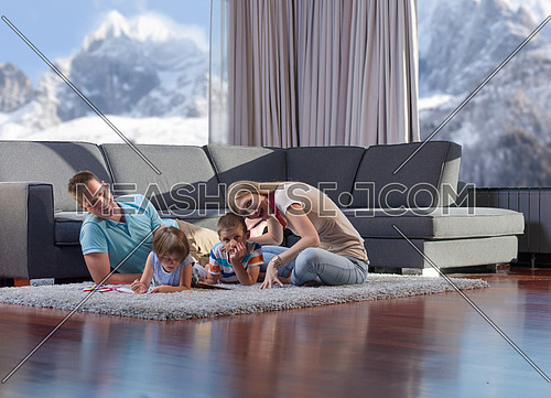 Happy Young Family Playing Together with tablet at home sitting on the floor