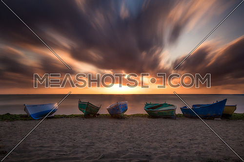 small rowing boats on a sandy beach at sunset