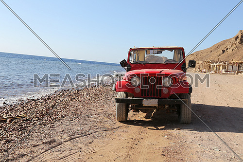 Red Old Jeep stop beside the sea on sandy beach with a mountain and a camp behind, at day