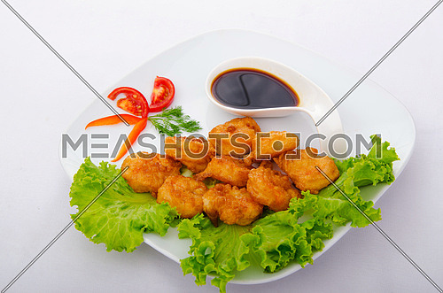 Breaded chicken pieces served with sauce