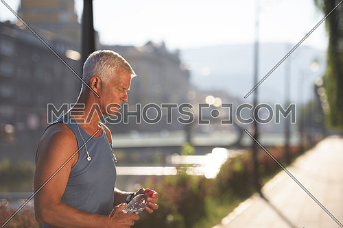 handsome senior jogging man drinking fresh water from bottle after mornig run