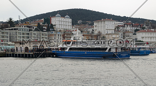 Istanbul, Turkey - March 3, 2013: Buyukada (Princess Island) Ferry Terminal with passengers riding a ferry and summer houses, and green mountains in the background, Istanbul, Turkey