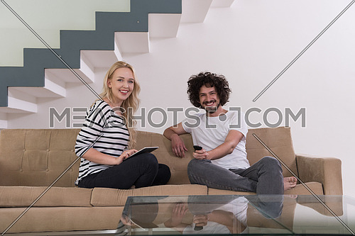 Young couple relaxes on the sofa in the luxury living room, using a tablet and remote control