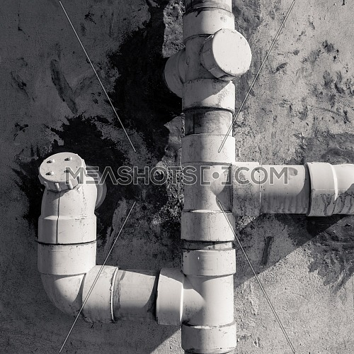 Plastic drainage pipes on white gauge stone wall