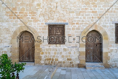 Two weathered wooden arched doors and one closed rusted wrought iron window on bricks stone wall and tiled stone floor