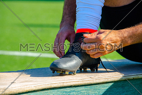 A close up on  football sports shoe athlete tying his shoe lace