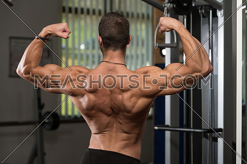 Portrait Of A Physically Fit Young Man - Flexing Muscles