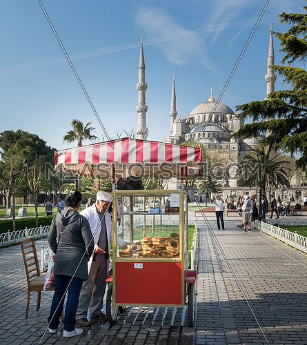 Istanbul, Turkey - April 16, 2017: Tourist buying fast food meal from a traditional Turkish Simit (Bagel) cart with Blue Square in the background