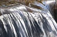 Brook or river running water stream flow with small rift over the stone shelf in bright sunny day time, close up