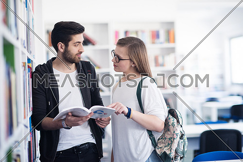 happy students couple in school  library have discussion about book