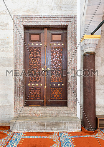 Wooden aged engraved door and marble wall, Suleymaniye Mosque, Istanbul, Turkey