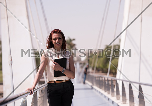 young business woman working on tablet computer at modern bridge business in motion concept