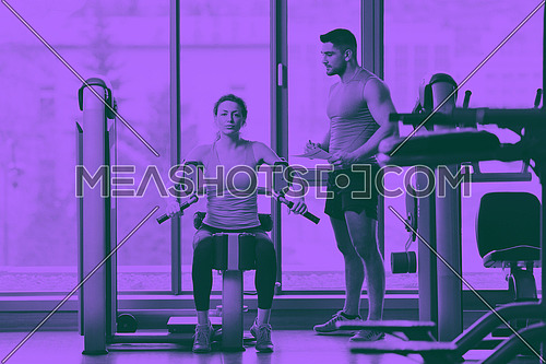 Gym woman exercising with her personal trainer duo tone