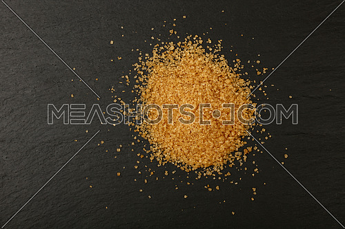 Close up pinch of brown cane sugar spilled on black slate board, elevated top view, directly above