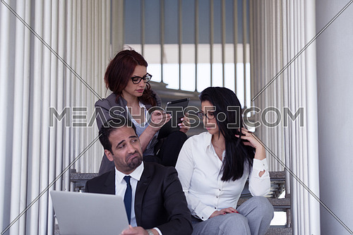 Young business executive sitting on the steps of a corporate offices building working with laptop and feeling unhappy while colleagues are sitting with him working with tablet