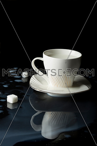 close up shot for a cup of milk put on black reflective surface and milk is poured around cup with two cube of sugar.