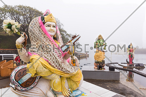 Hindu staues in a temple (Grand Basin), in the day with mist ,create mystical atmosphere.Mauritius