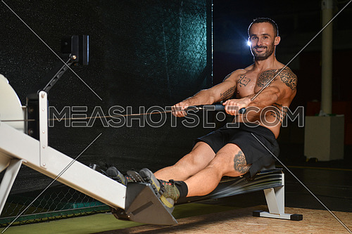 Young Strong Man In The Gym And Exercising Back On Machine - Muscular Athletic Bodybuilder Fitness Model Exercise