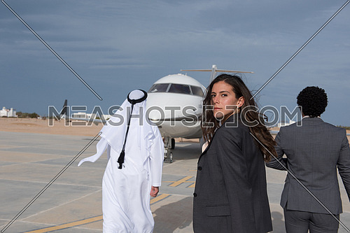 young successful middle eastern business woman walking with Arab business partner in front of private airplane