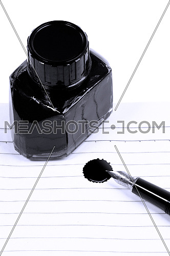 classic black fountain pen on open notebook with ink bottle with stain on page,blue filter
