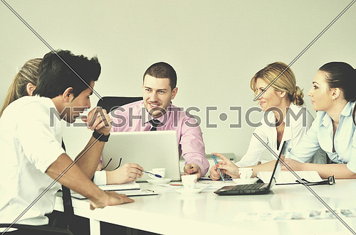 Group of young business people sitting in board room during meeting and discussing with paperwork