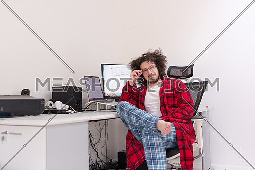 young graphic designer in bathrobe working at home office using computer