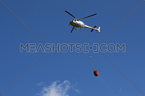 Firefighting helicopter with water bucket and trail of drops seen from below against blue sky