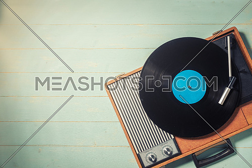 Vintage gramophone with a vinyl record on green wooden table, top view and copy space.