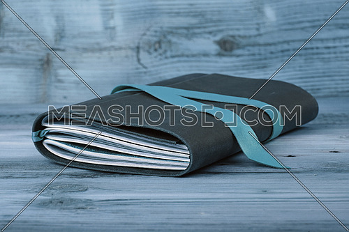 Handmade paper diary notebook in leather cover with bookmark over old vintage wooden table surface background, blue tone