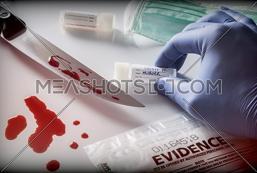 Scientist takes samples of a knife at the scene of a crime, conceptual image, horizontal composition