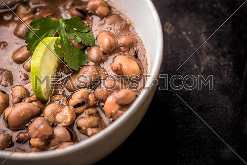 Foul Mesdames egyptian breakfast in a white bowl isolated on a black background