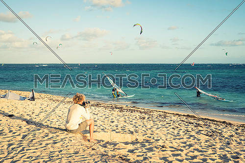 Travel photographer  taking pictures sitting on the beach during event of kitesurfing